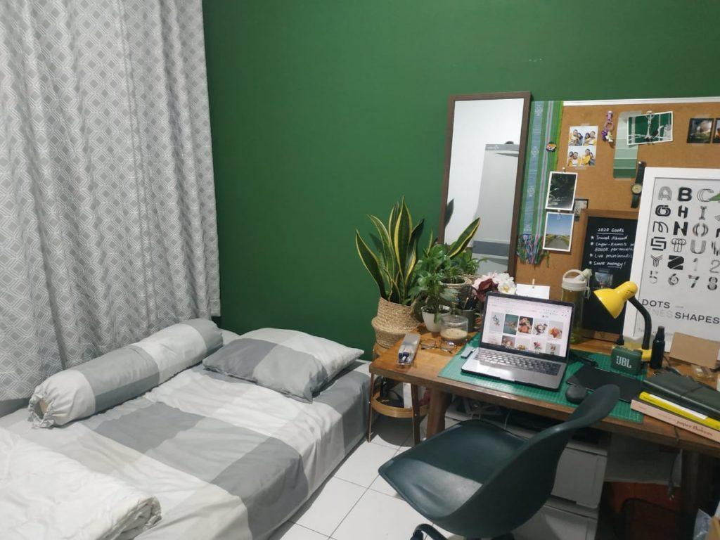 menata kamar kos yang rapi dan cat warna hijau tua yang sejuk bersifat menenangkan.